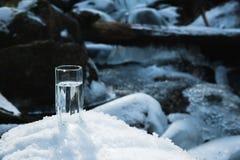 Ett genomskinligt glass exponeringsglas med att dricka bergvattenställningar i snön mot en bakgrund av ett rent frostberg Arkivbild