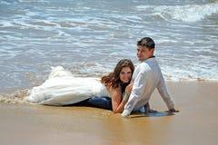 Ett gift par ligger på sanden på stranden av Indiska oceanen Gifta sig och bröllopsresa i vändkretsarna på ön royaltyfri bild