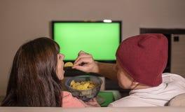 Ett gift par sitter hemma på soffan i aftonen, hållande ögonen på TV och äter chiper arkivbild
