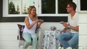 Ett gift par som dricker te i trädgården av ett landshus arkivfilmer
