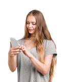 Ett gladlynt, le och en lycklig flicka med att charma långt blont hår rymmer en telefon som isoleras på en vit bakgrund Arkivfoton