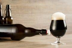 Ett glass brunt öl, på tabellen Royaltyfria Bilder