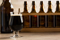 Ett glass brunt öl, på tabellen Arkivfoton