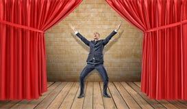 Ett glat affärsmananseende på en träetapp mellan röda gardiner i en seger poserar royaltyfri foto