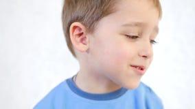 Ett glat barn sätter långsamt hans finger i näsan lager videofilmer