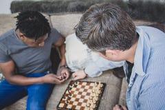 Ett glat par som inomhus tycker om tid hemma och att spela schack royaltyfri fotografi