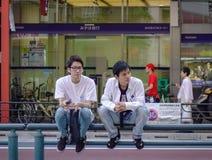 Ett glat par som sitter på gatan av Tokyo royaltyfri foto