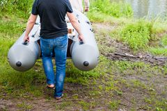 Ett grått uppblåsbart fartyg på flodbanken i vår och sommar Mannen bär ett uppblåsbart fartyg, Royaltyfri Fotografi