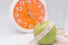 Ett grönt äpple med ett mäta band som slås in runt om det för Co Arkivfoto