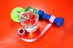 Ett grönt äpple med ett mäta band, hantlar Ett läckert hem gjorde drinken med nya bär i ett exponeringsglas Royaltyfri Bild