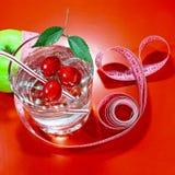 Ett grönt äpple med ett mäta band Ett läckert hem gjorde drinken med nya bär i ett exponeringsglas Arkivfoto
