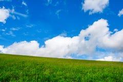 Ett grönt fält i bergen med krämiga moln Arkivbild