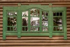 Ett grönt fönster med reflexioner på den yttre byggnadsväggen för brun timmer Dekorativ traditionell träram royaltyfria foton
