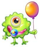 Ett grönt monster behandla som ett barn med en ballong Royaltyfri Foto