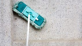 Ett grönt smutsar ner folkhop, eller bomullstoppen lutar på den smutsiga betongväggen Golvgolvmoppet är den van vid rengöringen g royaltyfri fotografi
