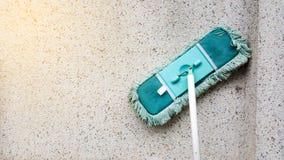 Ett grönt smutsar ner folkhop, eller bomullstoppen lutar på den smutsiga betongväggen Golvgolvmoppet är den van vid rengöringen g arkivbild