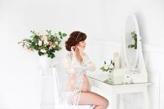 Ett gravid kvinnasammanträde på en dressingtabell i budoarklänningen Royaltyfri Foto