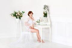 Ett gravid kvinnasammanträde på en dressingtabell i budoarklänningen Royaltyfria Bilder