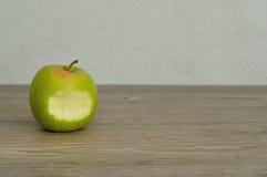 Ett grönt äpple med en tugga som ut tas Royaltyfri Bild