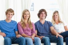 Ett grupp människorsammanträde tillsammans på soffan Royaltyfria Foton