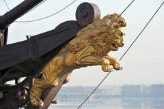 Ett guld- diagram av ett lejon på pilbågen Royaltyfri Bild
