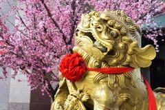 Ett guld- Lion Statue Placed Near A dekorerat träd royaltyfri foto