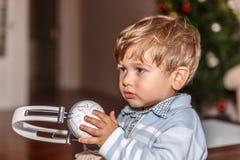 Ett gulligt barn är klart att lyssna till musik med en stor hörlurar med mikrofon medan i vardagsrummet arkivbild