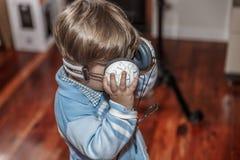 Ett gulligt barn är klart att lyssna till musik med en stor hörlurar med mikrofon medan i vardagsrummet fotografering för bildbyråer