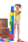 Ett gulligt barn som spelar med leksaker En idérik flicka med leksak-kvarter som isoleras på en vit bakgrund Utbildnings- och utv royaltyfri foto