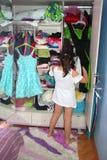 Ett gulligt barn som väljer klänningen Arkivbild