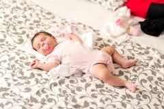 Ett gulligt behandla som ett barn att ligga och att sova på en grå filt royaltyfria foton