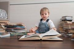 Ett gulligt behandla som ett barn och en stor bok royaltyfri foto