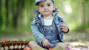 Ett gulligt behandla som ett barn äpplepojke little Litet barn i grov bomullstvilldräkt och ett lock lager videofilmer