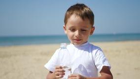 Ett gulligt litet behandla som ett barn drinkvatten från en flaska, medan stå på stranden på en varm solig dag Fritid och lekar i lager videofilmer