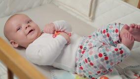 Ett gulligt litet behandla som ett barn ser in i kameran och är lyckligt på ett vitt sängark stock video