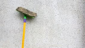 Ett gult smutsar ner folkhop, eller bomullstoppen lutar på den smutsiga betongväggen Golvgolvmoppet är den van vid rengöringen go royaltyfri fotografi