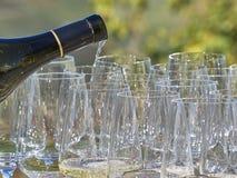 Ett hällande vin för flaska in i några exponeringsglas med det Langhe landet arkivfoton