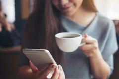 Ett härlig asiatisk kvinnainnehav och användasmartphone, medan dricka kaffe i kafé Royaltyfria Foton