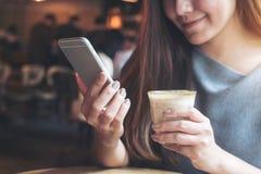 Ett härlig asiatisk kvinnainnehav och användasmartphone, medan dricka kaffe i kafé Fotografering för Bildbyråer