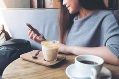 Ett härlig asiatisk kvinnainnehav och användasmartphone, medan dricka kaffe i kafé Royaltyfria Bilder
