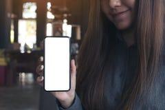 Ett härligt asiatiskt kvinnainnehav och en svart mobiltelefon för visning med den tomma vita skrivbords- skärmen i kafé Royaltyfri Bild