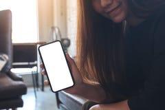Ett härligt asiatiskt kvinnainnehav och en svart mobiltelefon för visning med den tomma vita skrivbords- skärmen i kafé Royaltyfri Foto