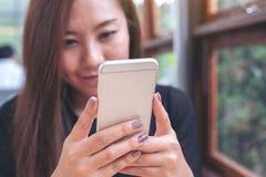 Ett härligt asiatiskt kvinnainnehav och genom att använda och se den smarta telefonen med mening lyckligt arkivfoton