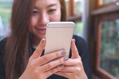 Ett härligt asiatiskt kvinnainnehav och genom att använda och se den smarta telefonen med mening lyckligt royaltyfri foto