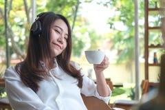 Ett härligt asiatiskt kvinnaslut henne ögon och att lyssna till musik med headphonen, medan dricka kaffe med mening lyckligt, och fotografering för bildbyråer