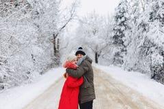 Ett härligt familjpar som går på en snöig väg i träna royaltyfria bilder
