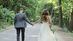 Ett härligt gift par som går ner parkera och innehavet deras händer bröllop för klänningfragmentbeställning Gröna träd på bakgrun lager videofilmer
