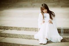 Ett härligt kvinnasammanträde på en stege som läser en bok Arkivfoto