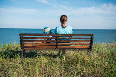 Ett härligt kvinnawuthbarn som framme ser till havet av den härliga hav- och himmelsikten royaltyfria bilder