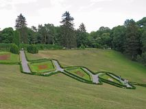 Ett härligt landskap av en grön gräsmatta i en parkera på en lutning med banor som går mellan figurerade rabatter med folk Arkivfoto